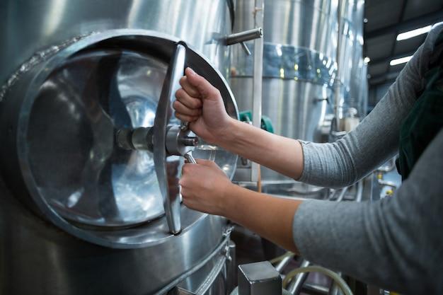Работница фабрики поворачивает колесо управления резервуара