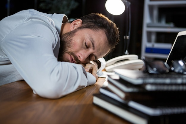Уставший бизнесмен спит на столе