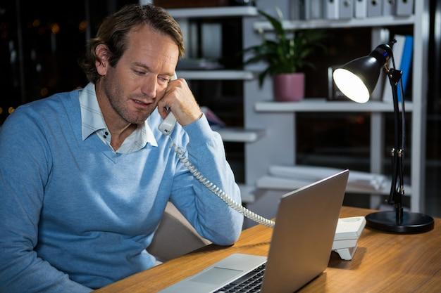 Бизнесмен разговаривает по телефону во время работы в офисе