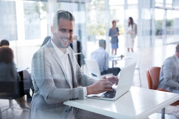 Улыбающийся бизнесмен, используя ноутбук в офисе