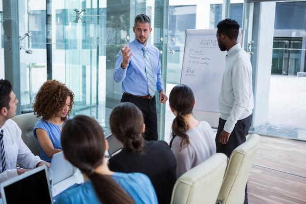 Бизнесмен обсуждает на белой доске с коллегами