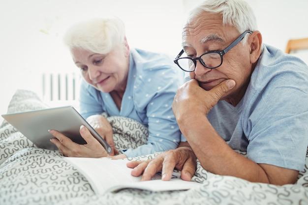 Пожилые супружеские пары, читая книгу и с помощью цифрового планшета на кровати