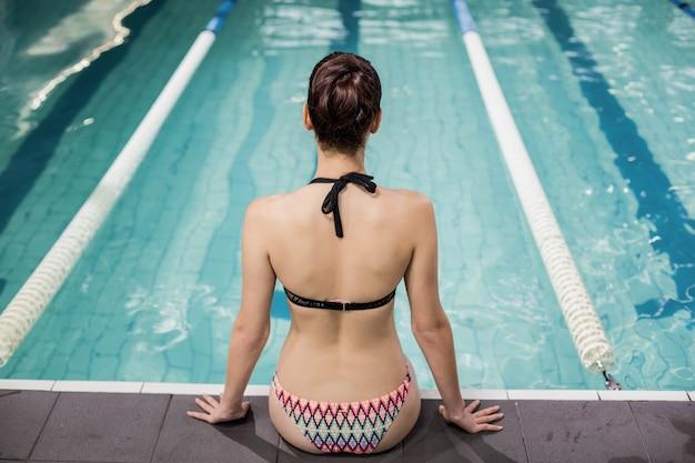 プールサイドに座っている水着でブルネットの背面図