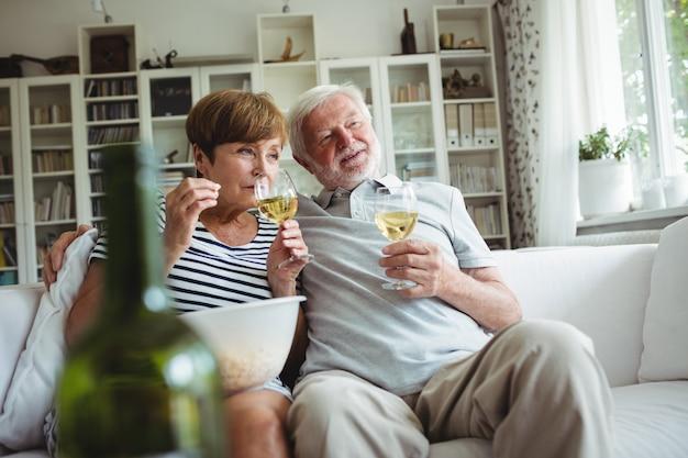 ワインのグラスを持っている年配のカップル