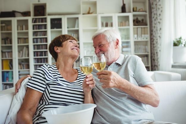 年配のカップルがワインのグラスを乾杯