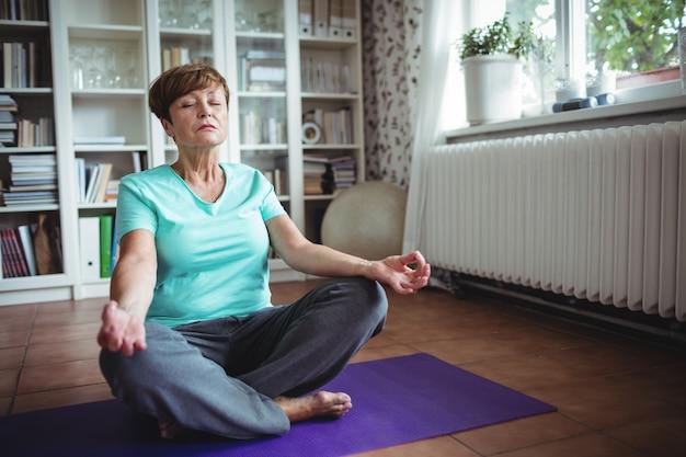Пожилая женщина медитирует в позе лотоса