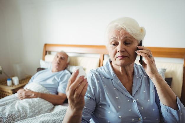 Старшая женщина смотря бутылку пилюльки и говоря на телефоне