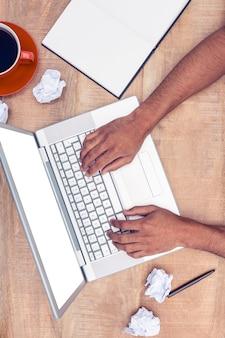 オフィスの机でラップトップを使用して強調した実業家のオーバーヘッド