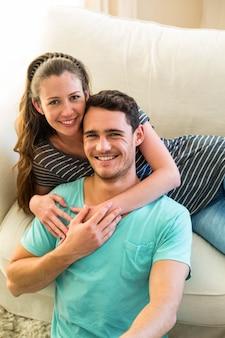 自宅のリビングルームで一緒に楽しんで幸せな若いカップルの肖像画