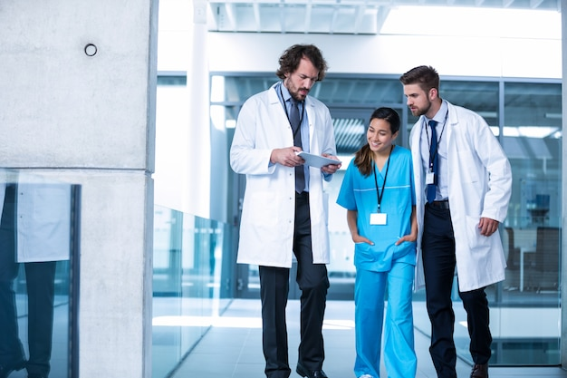 同僚との議論を持つデジタルタブレットを保持している医師