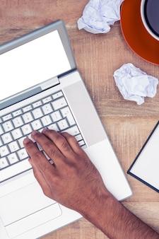 オフィスの机でラップトップを使用して強調した実業家の画像をトリミング