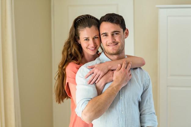 リビングルームで抱きしめる幸せな若いカップルの肖像画