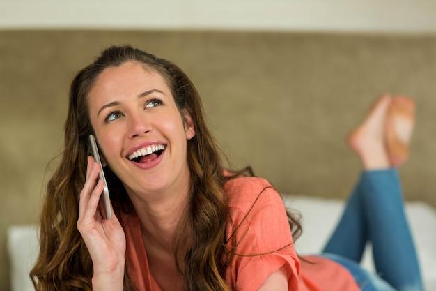 笑顔とベッドに横たわっている間電話で話している若い女性