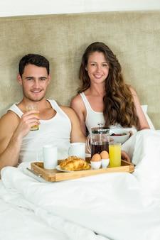 Портрет молодой пары завтрака на кровати в спальне