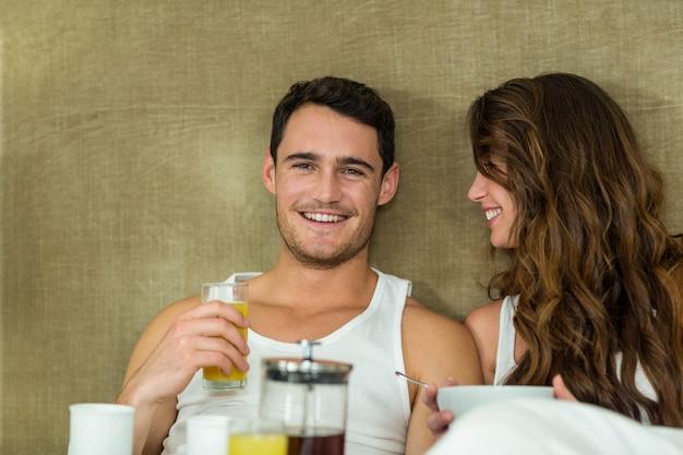 寝室のベッドで朝食を持っている若いカップル
