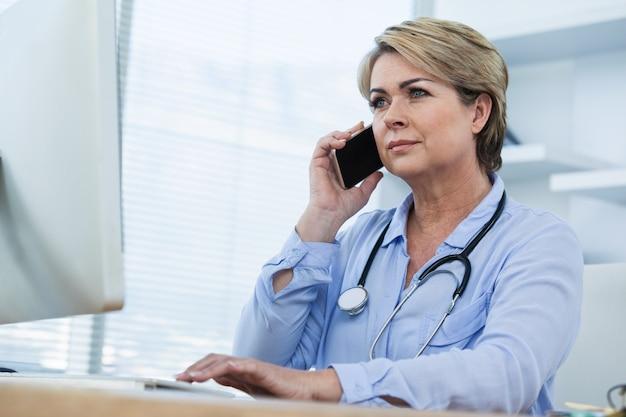 Женский доктор разговаривает по мобильному телефону во время работы над компьютером