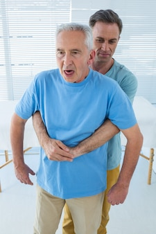 医師から背中の治療を受けるシニアの患者