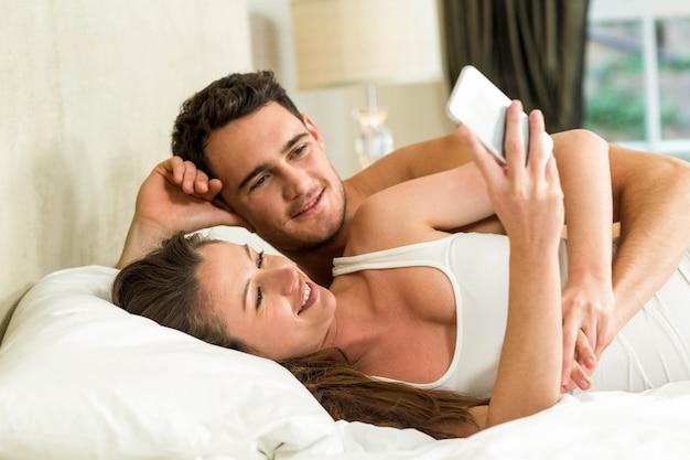 スマートフォンを見て、ベッドでリラックスした若いカップル