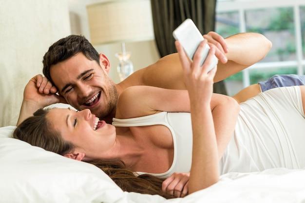 若いカップルがスマートフォンを見ているとベッドの上で楽しんで