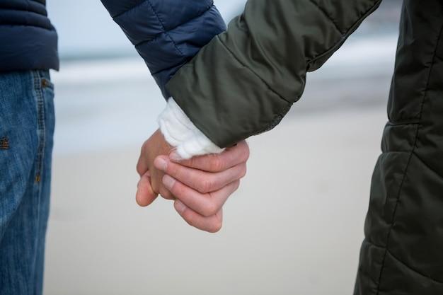 ビーチで手を繋いでいるカップルのクローズアップ