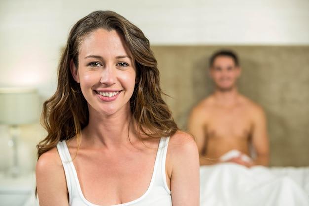 カメラと彼女の後ろにベッドの上に座っている男に笑みを浮かべて美しい女性