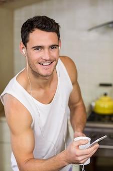 若い男が台所で家で音楽を聴く