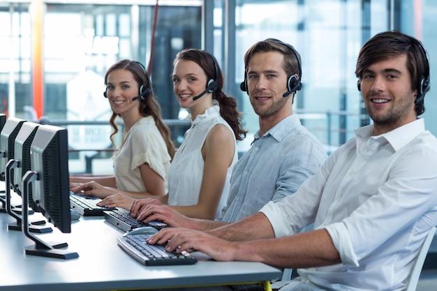 Руководители предприятий с гарнитурами, используя компьютер в офисе