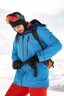 スキーヤーは彼のバックパックベルトを締めます