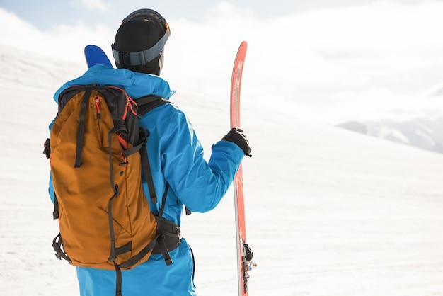 美しい雪に覆われた山々を見てスキーヤー