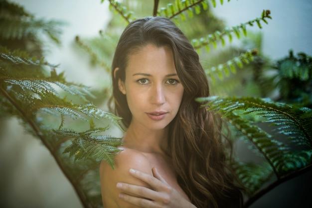 緑の植物に対して屋外に立っている美しい女性