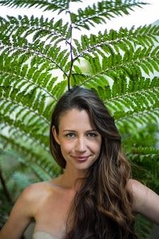 緑の植物に対して屋外に立っている美しい女性の肖像画