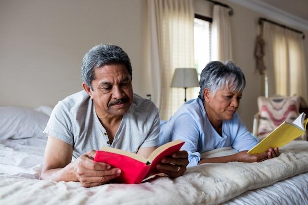 Пожилая пара читает книги на кровати