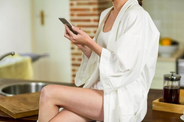 ワークトップの上に座って、台所でテキストメッセージを入力してバスローブで美しい女性