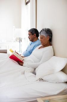 Пожилая пара читает роман в гостиной