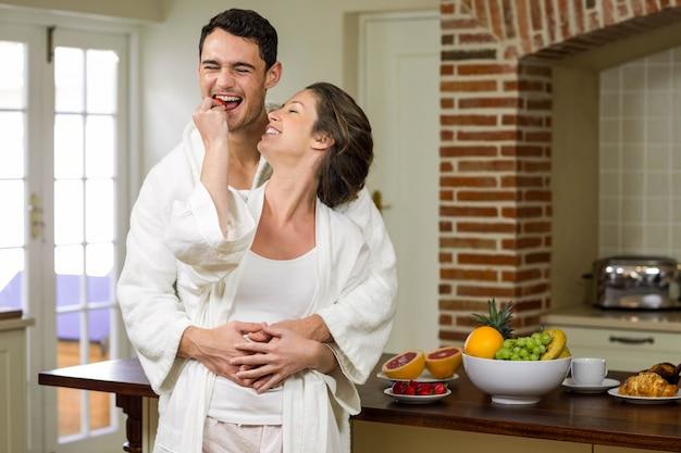 女性が台所で彼にイチゴを供給しながら抱きしめる男