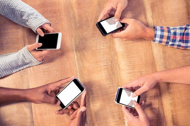 オフィスの机でスマートフォンを使用しているビジネス人々の高角度のビュー