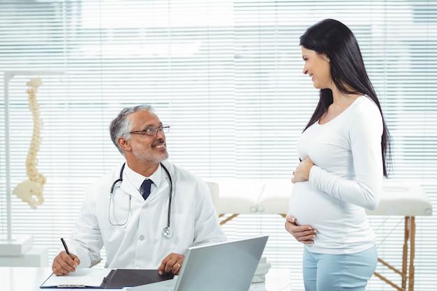 妊娠中の女性が健康診断中に診療所で医師と対話します。