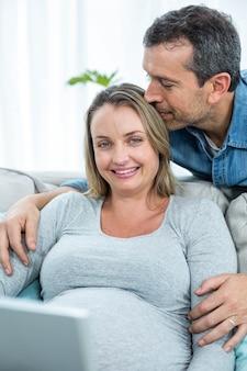 リビングルームのソファーに一緒に座っているカップル