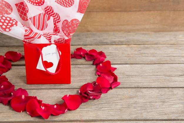 ハート型の赤いバラの花びらに囲まれたギフトボックス