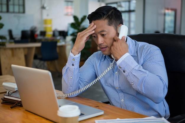 Разочарованный руководитель бизнеса разговаривает по телефону