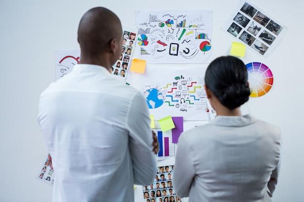 Вид сзади графических дизайнеров, глядя на графики и диаграммы