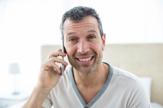 男はベッドの上に座っていると寝室でスマートフォンで話しています。