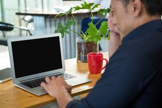 机に座ってラップトップを使用してビジネスエグゼクティブ