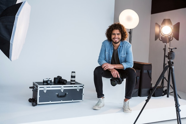 スタジオに座っている幸せな男性カメラマン