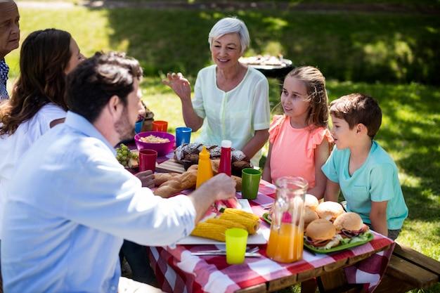 Счастливая семья много поколений обедает на столе