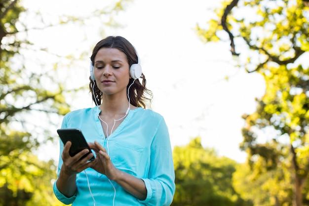 Женщина слушает музыку в мобильном телефоне