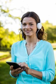 Музыка женщины слушая в мобильном телефоне на парке