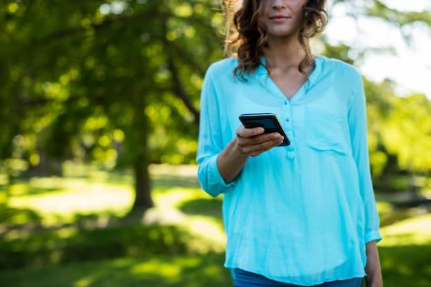 Средняя часть женщины с помощью мобильного телефона