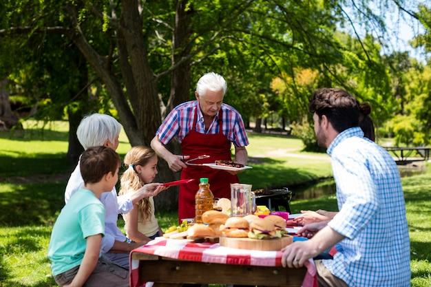 Старший мужчина, где подают барбекю для семьи в парке