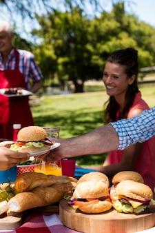 Отец передает тарелку бургера сыну в парке